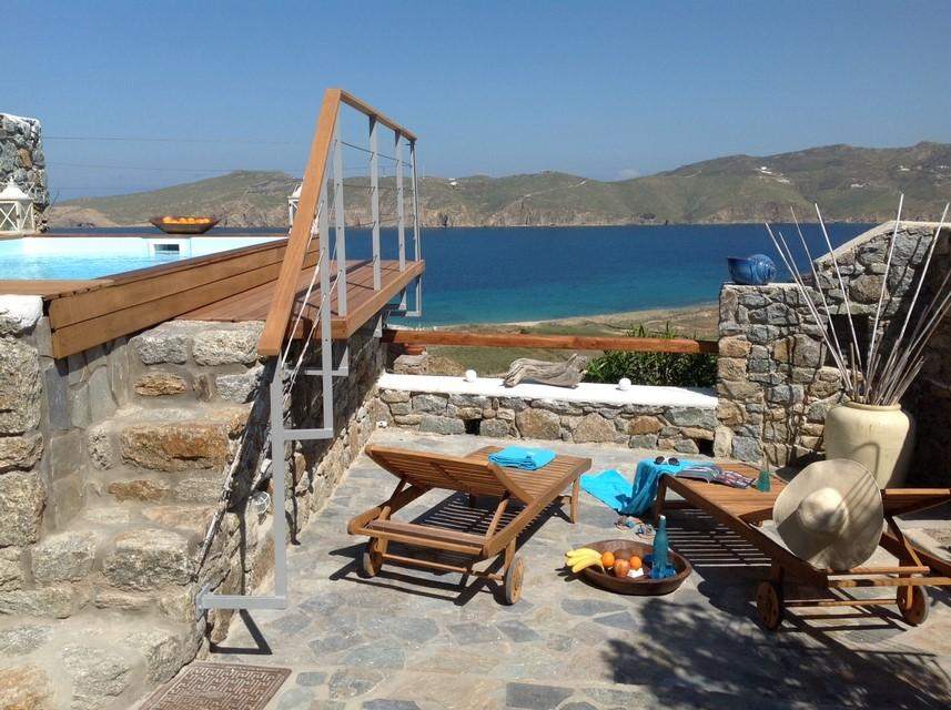 sunbathing on wooden deck chairs overlooking the sea, swimming pool and surrounded by natural expanse