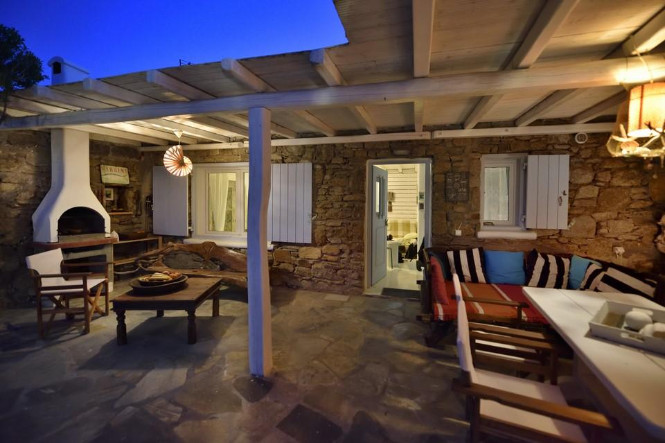 ideal space to enjoy summer nights with stone walls, fireplace and wooden garden furniture, white wooden canopy