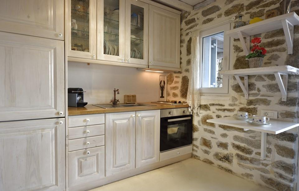 the ideal place to enjoy cooking is the kitchen with stone walls and wooden white kitchen elements decorated with potted flowers and a window that gives daylight