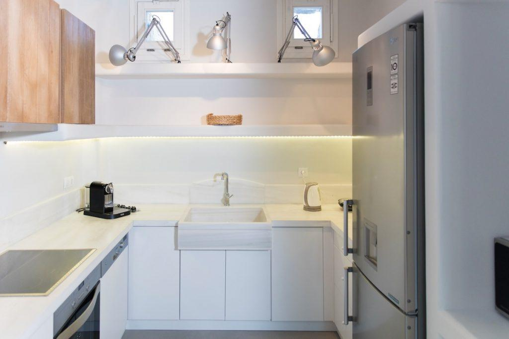 white wall room with huge fridge and coffee maker
