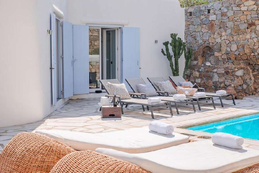 outdoor area with pool and comfortable sun loungers perfect for sunbathing