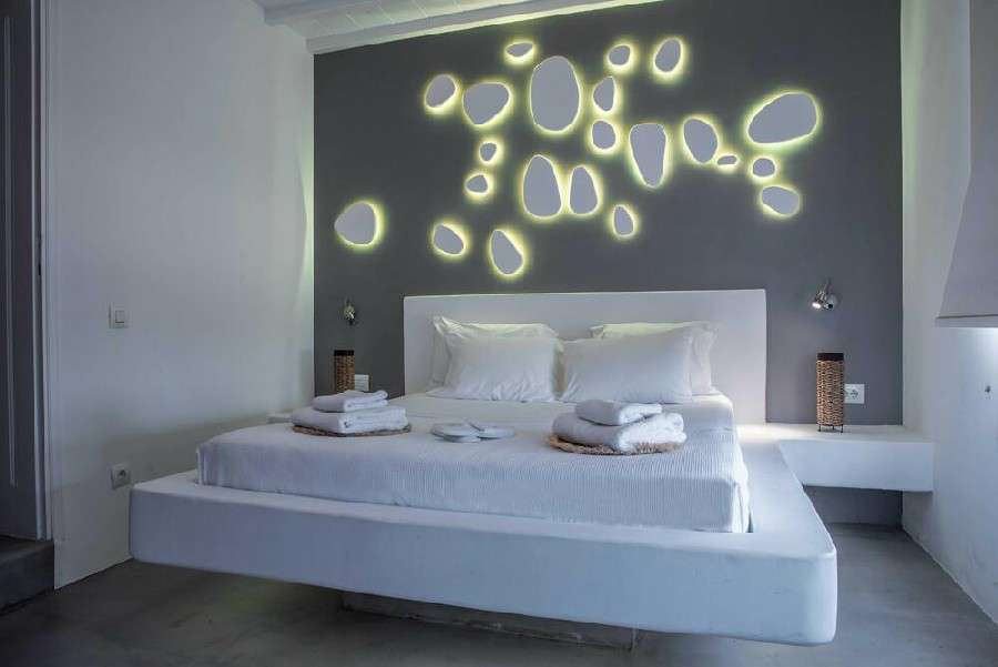 bedroom with walls lit by lamps for a romantic night
