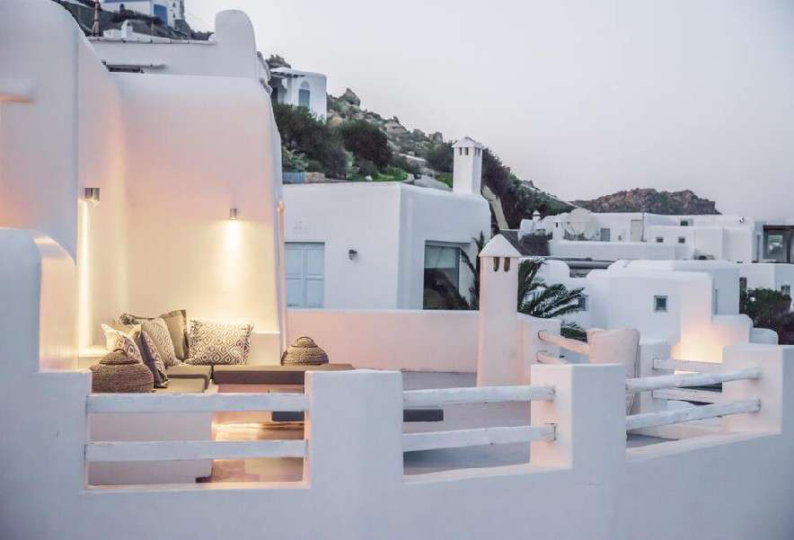 balcony with white walls and comfortable corner furniture ideal for enjoying a summer night