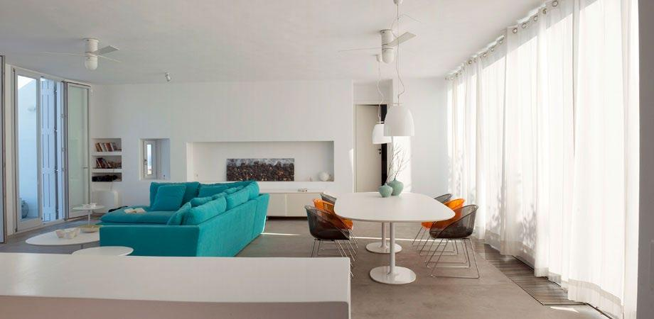modern designed living area with hanging chandelier and two cooling fans