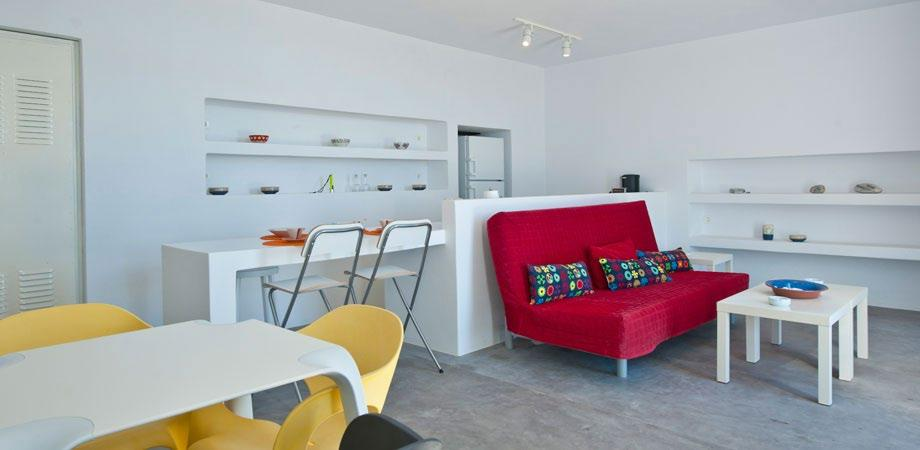 bright living space with red sofa and table with small chairs for kids to play