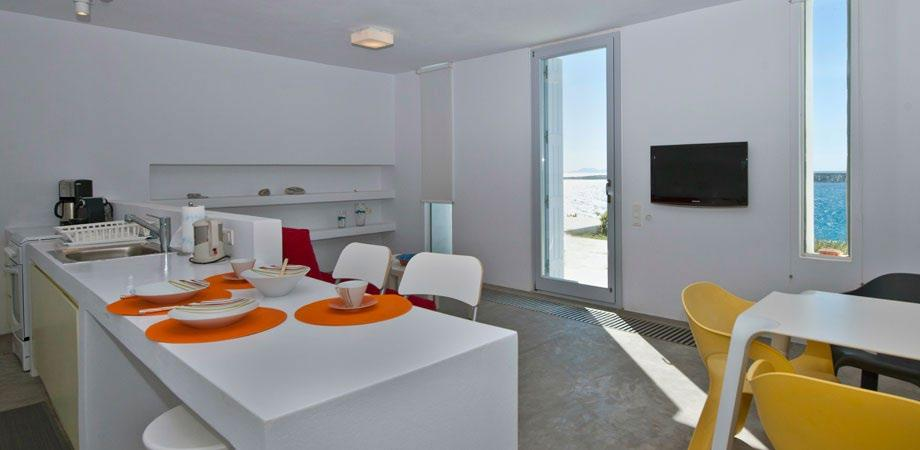 spacious living room with big sofa faced directly at window wall sea view with tables to eat meals