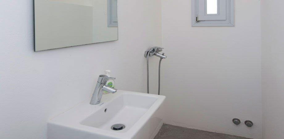 bathroom with ceramic sink square mirror and corner shower