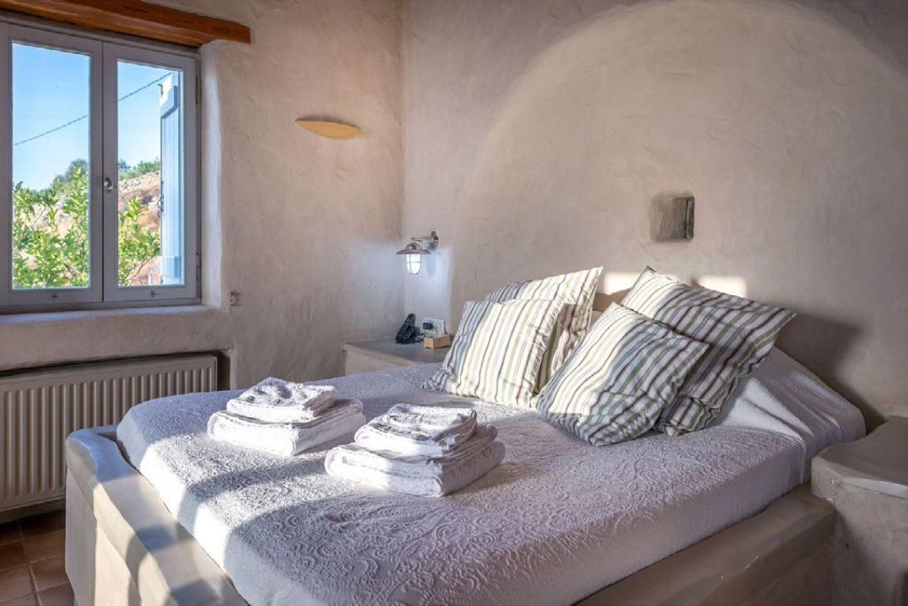 snug and cozy bedroom containing king size bed with clean towels on top