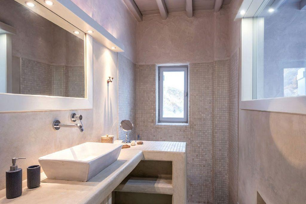 illuminated bathroom with elevated sink and big mirror
