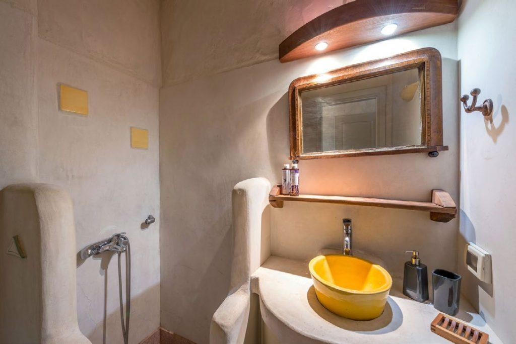 bright lamp and candle lighted bathroom with corner shower