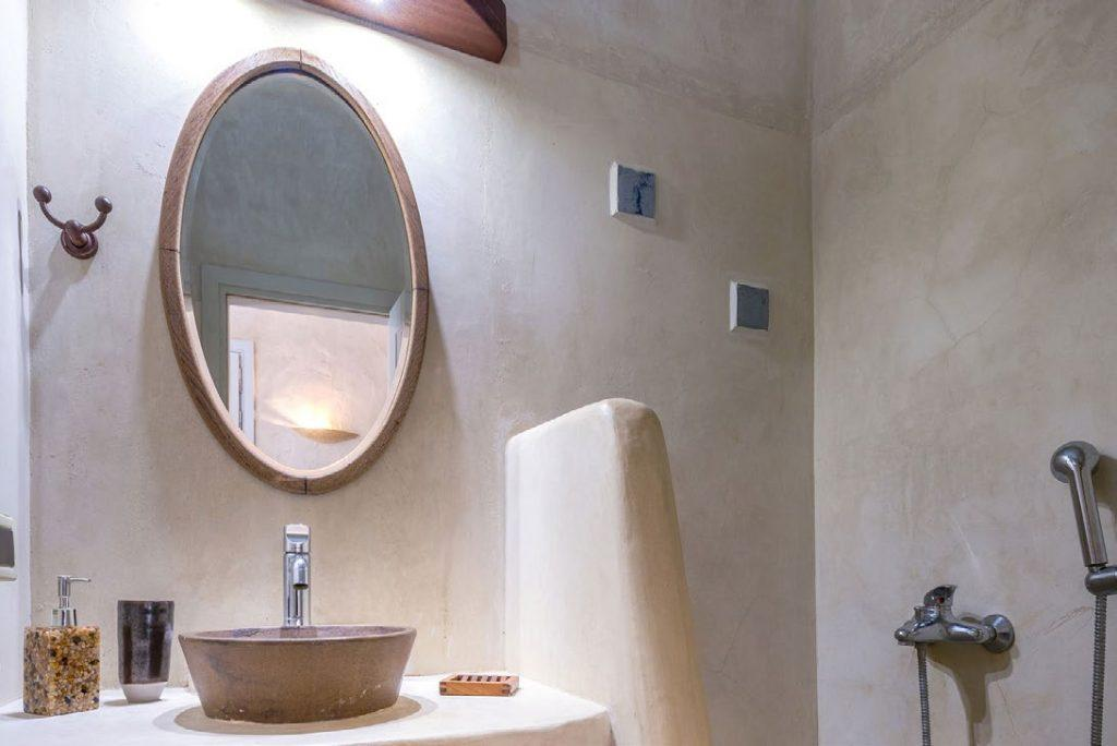 marble tiled lighted bathroom with egg shaped mirror