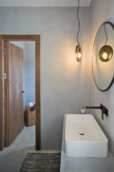 lamp lighted bathroom with elevated ceramic sink and round mirror
