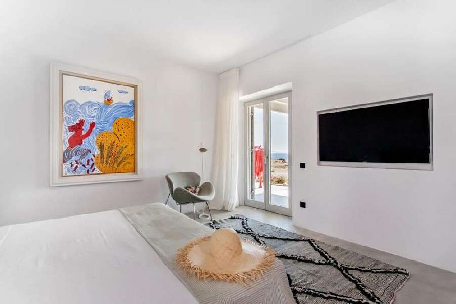 white spacious bedroom with wall painting wall mount TV and terrace window wall exit