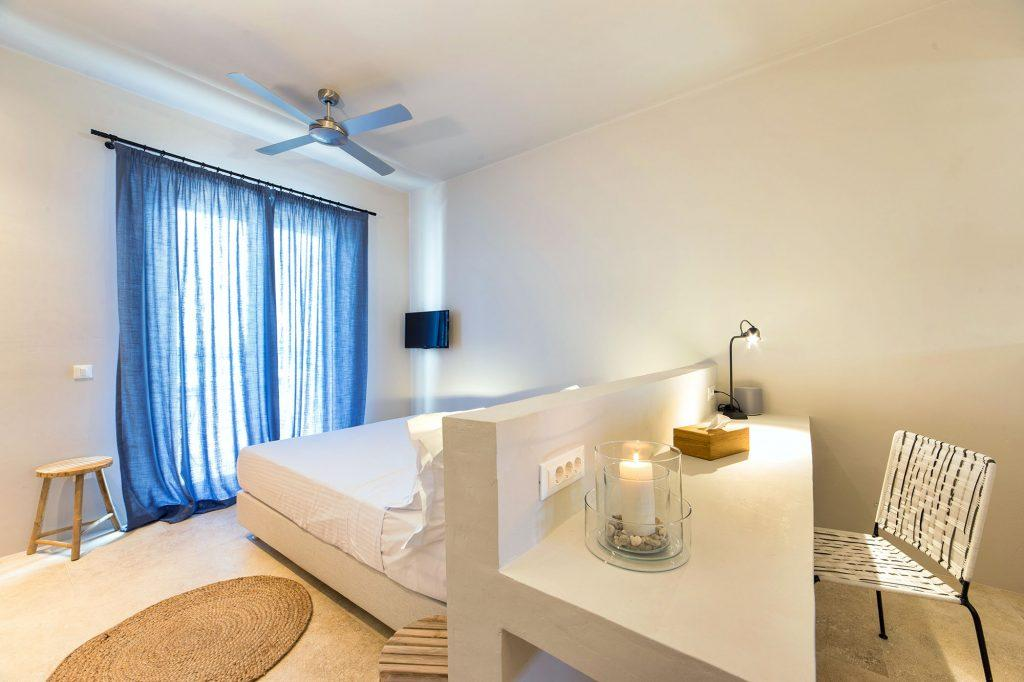white painted master bedroom containing king size bed TV and fan