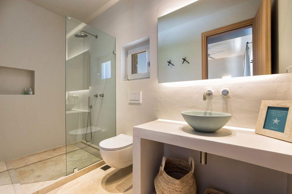 bathroom sink and open glass shower cabin