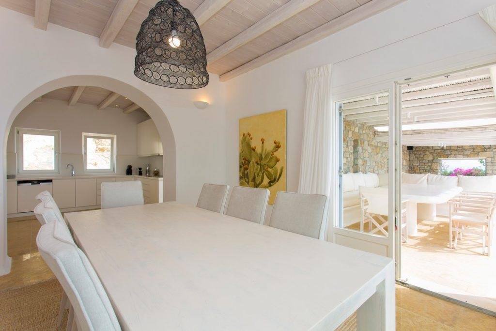 white dining table with comfortable chairs that fits perfectly into a modern kitchen