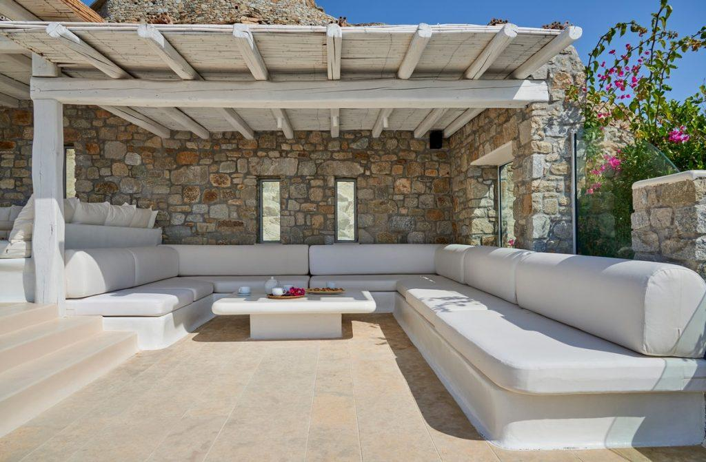 huge white sofa and table beneath porch and set against stone paved villa wall for you and your friends to get together