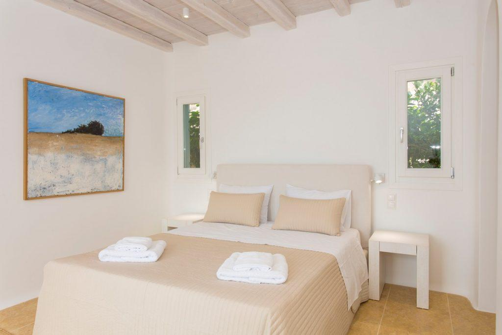 bedroom with beige bedspread and colorful painting
