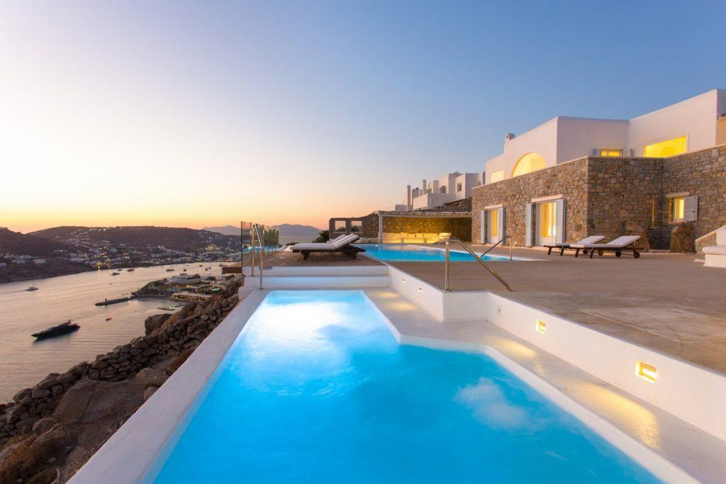 sunset over the sea and the illuminated city of Mykonos from a modern villa