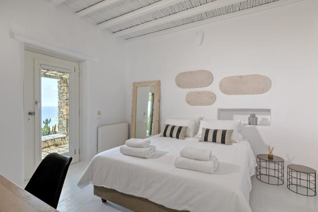 white wall bedroom with soft pillows and white sheets with enjoyable sea view