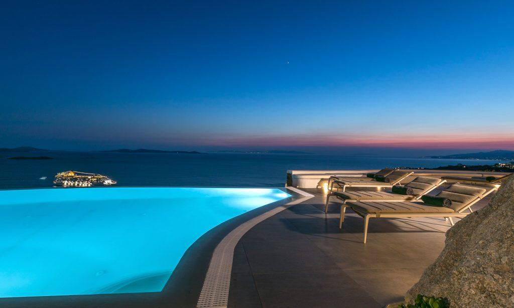 night view of a villa with a lighted pool and a view of the purple sky