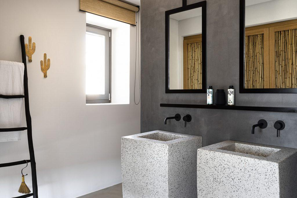 bathroom with ceramic sink and wall mirrors