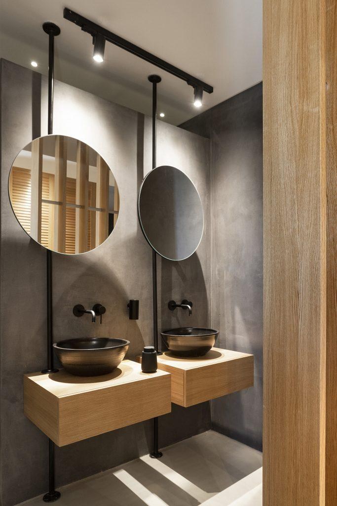 lit bathroom with round mirrors and sinks