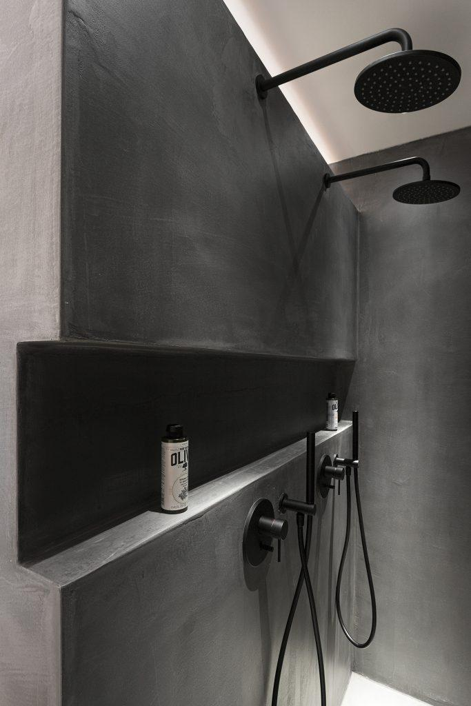 black wall bathroom with showers and soaps