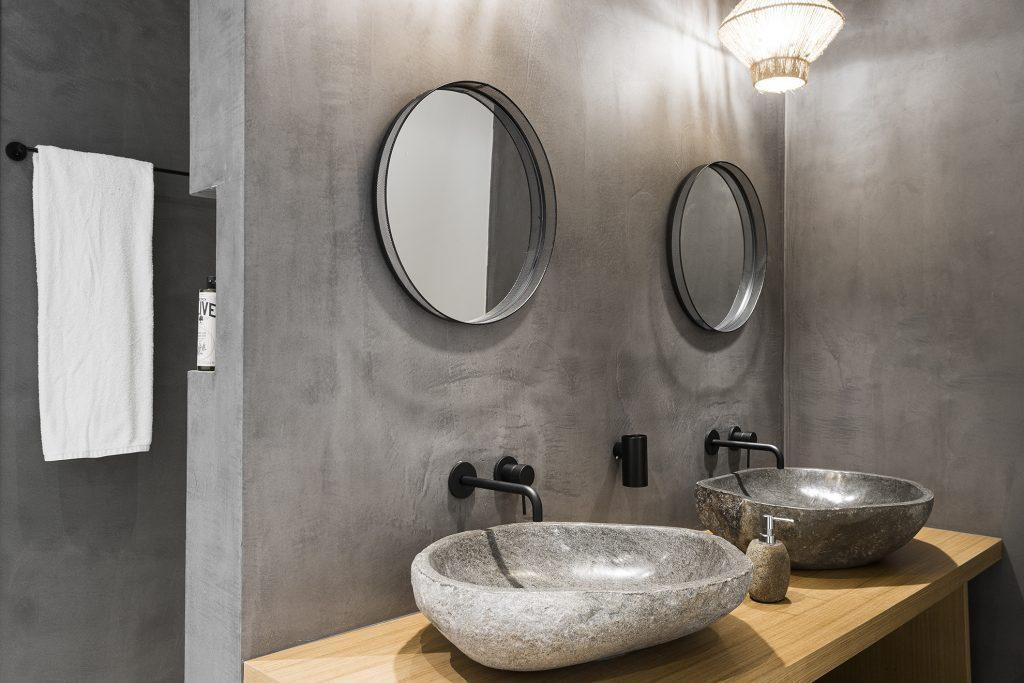 bathroom with round wall mirrors and ceramic sink