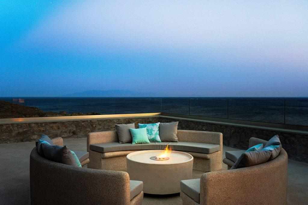 outdoor area with round soft couches and fireplace