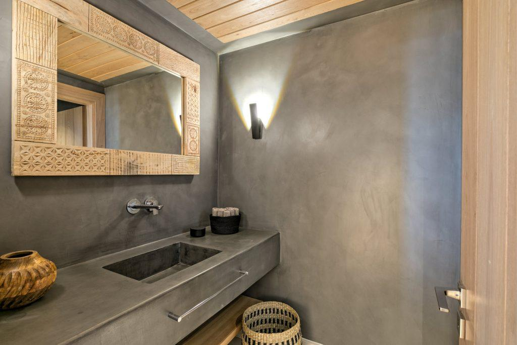 grey wall bathroom with lamps and wooden mirror