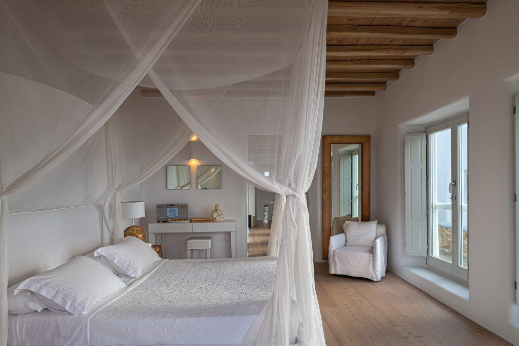 bedroom with king size bed and white curtains