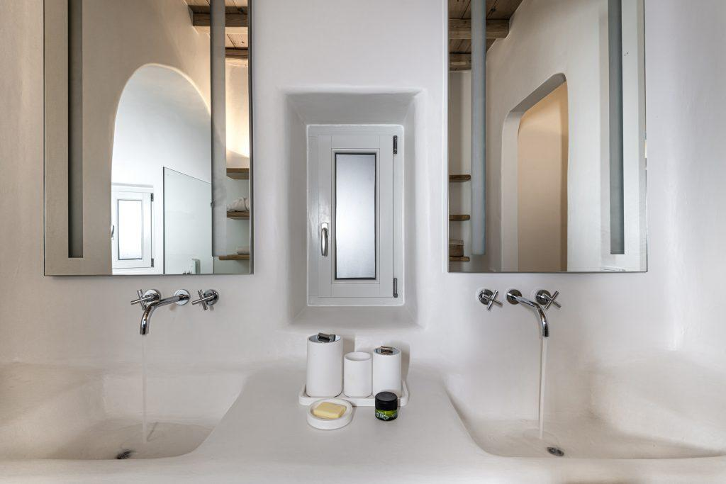 white wall bathroom with huge mirror and daylight from window