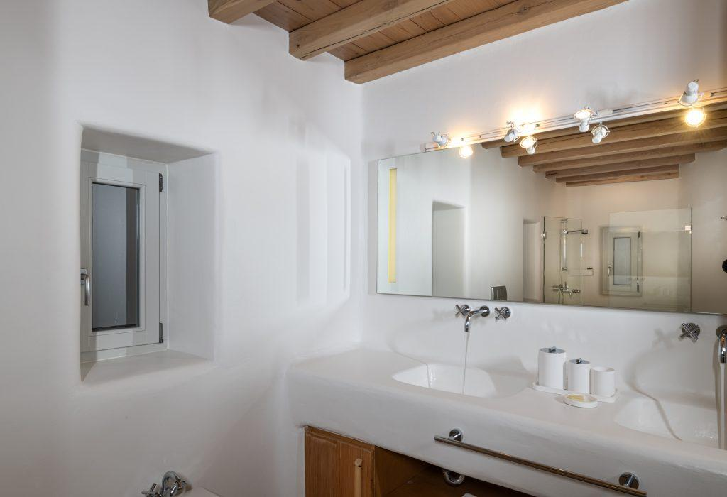 bathroom with two sinks and one big mirror with lights above