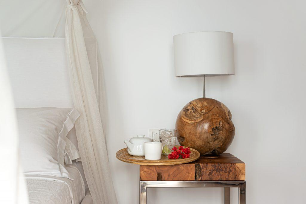 bedroom with nightstand next to bed with white sheets and pillows
