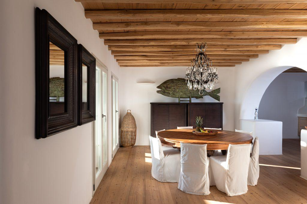 interior dining area with rounded wooden table and white chairs