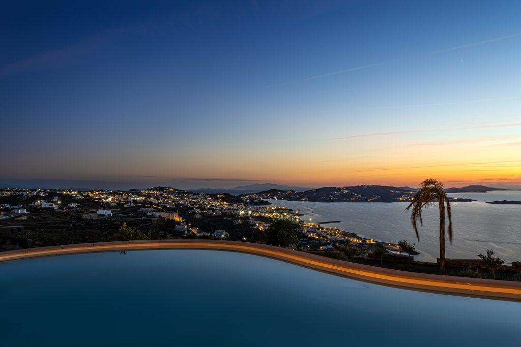 night view of a villa with a lighted pool and a view of the sky