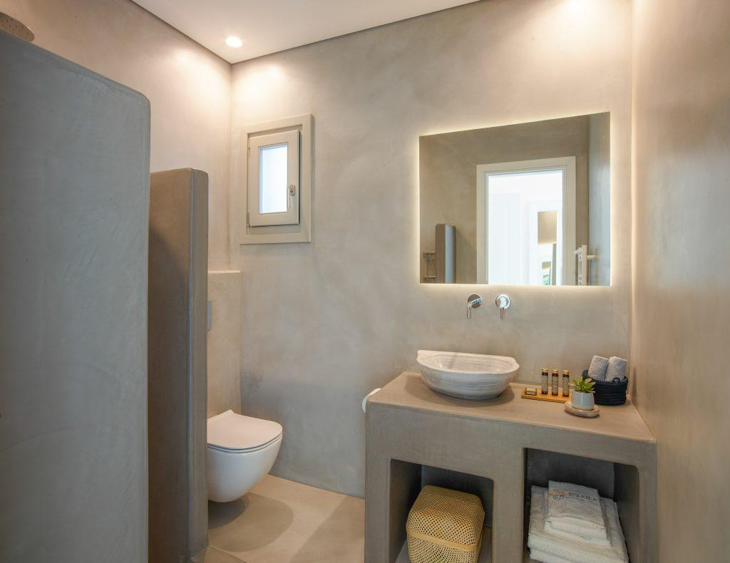 grey lit wall bathroom with toilet and shower