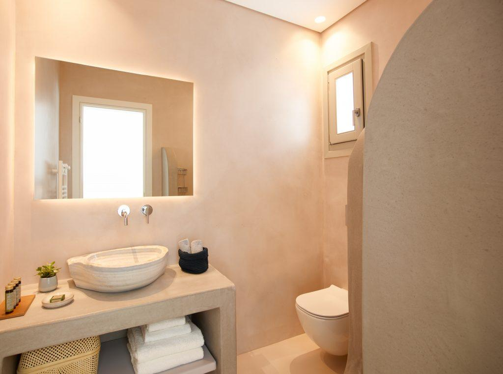 bathroom with huge lit wall mirror and ceramic sink