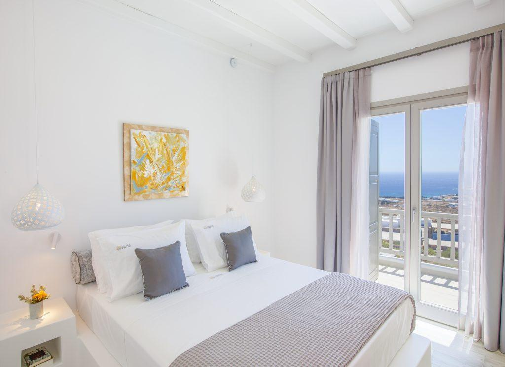white wall bedroom with curtains to protect from the sun