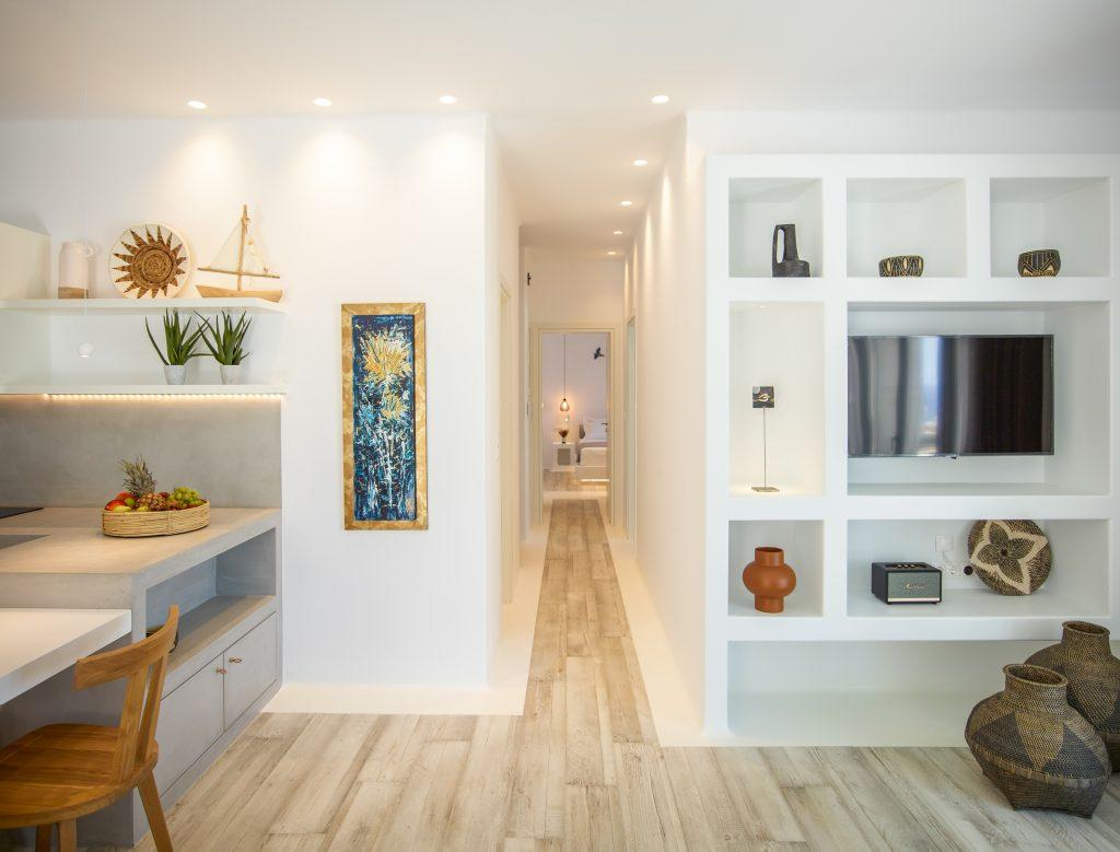 area with white wall shelfs and flat screen tv