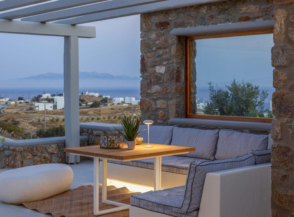outdoor dining area with wooden lit table and comfort bed