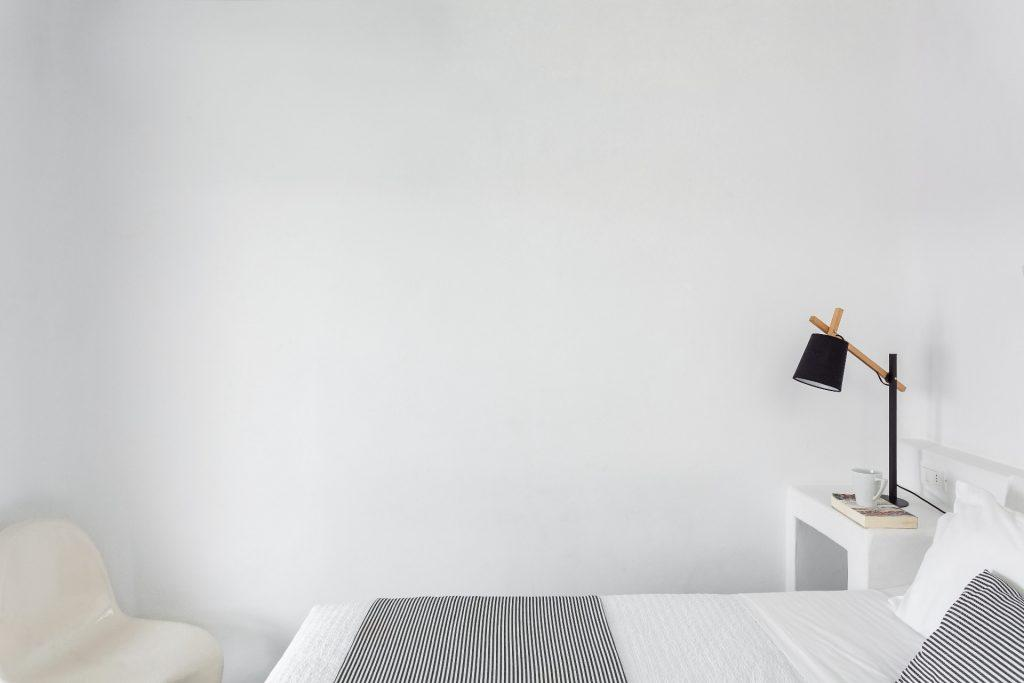 white wall bedroom with nigh stand and lamp