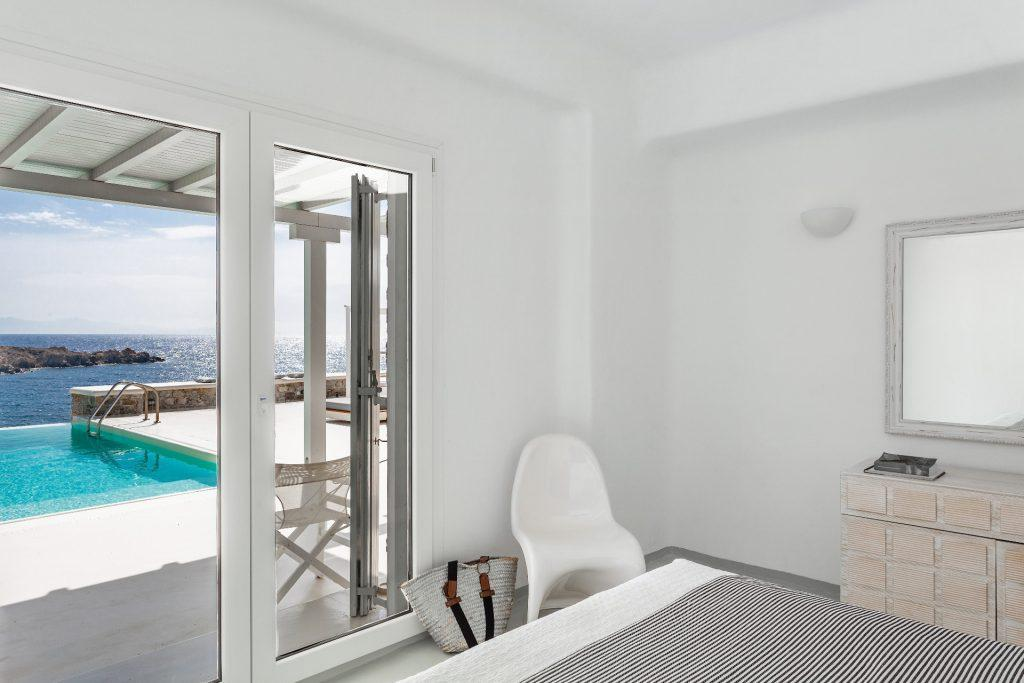 minimal designed bedroom with white chair and wall mirror