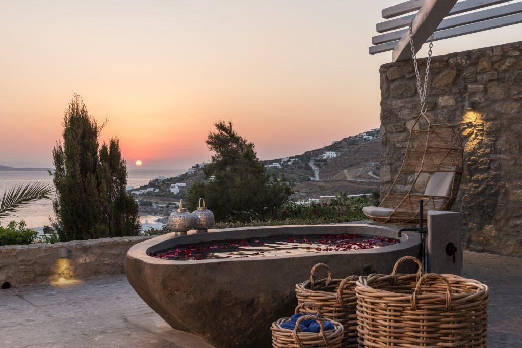 stone tub sprinkled with petals overlooking the enchanting sunset ideal for a romantic evening
