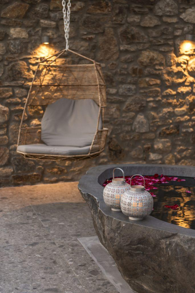stone tub sprinkled with petals ideal for a romantic evening