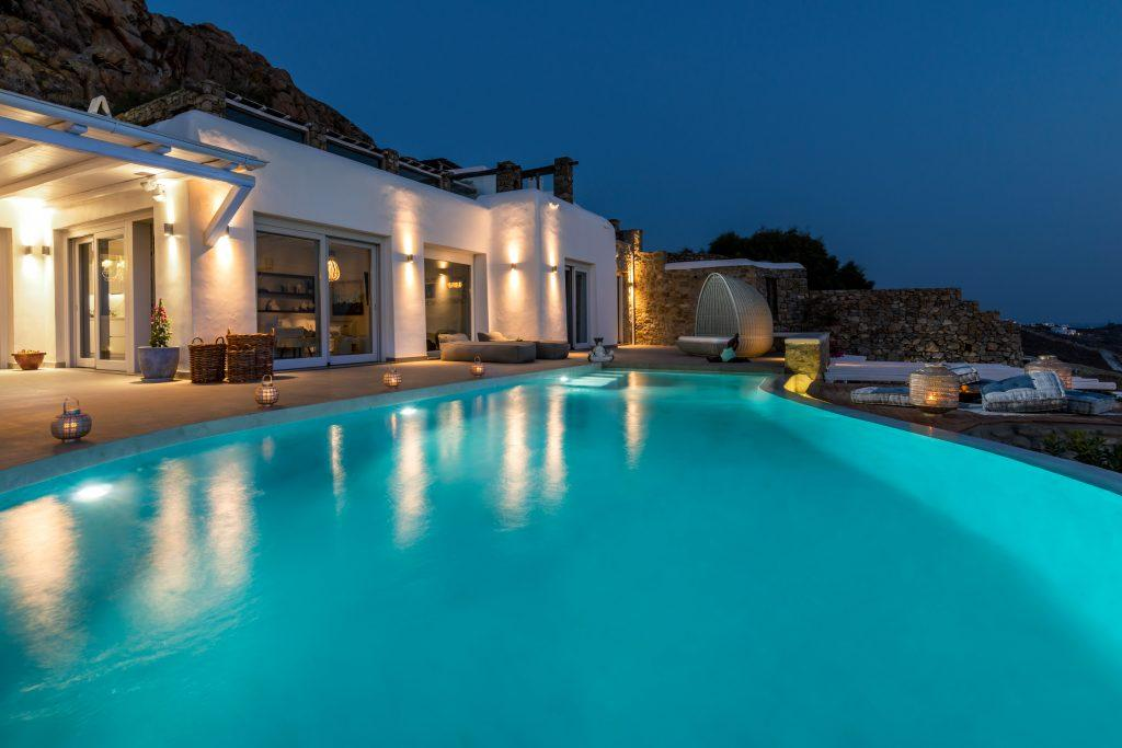 night view of the villa lit by lamps that emphasize its luxury