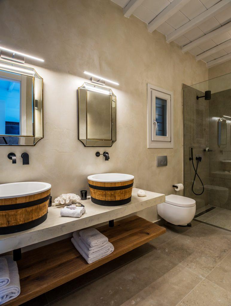 two mirrors with sinks and a glass shower