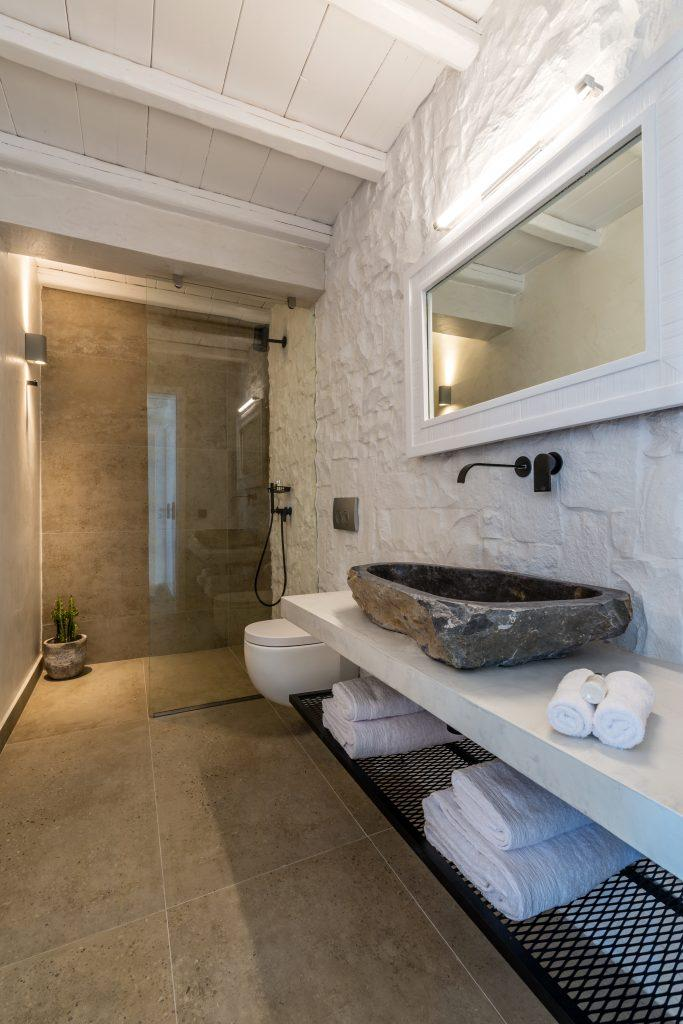 glass toscabin and a stone sink with a large mirror in a white frame