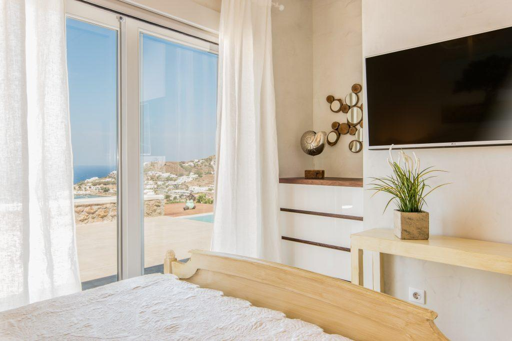 room with a large TV and a wooden comfortable bed